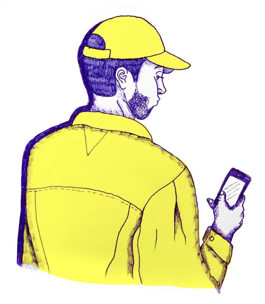 En person med kort mörkt hår har på sig gul jacka och gul keps. Hen står med ryggen mot oss och håller en mobil i sin hand som hen tittar ned på.