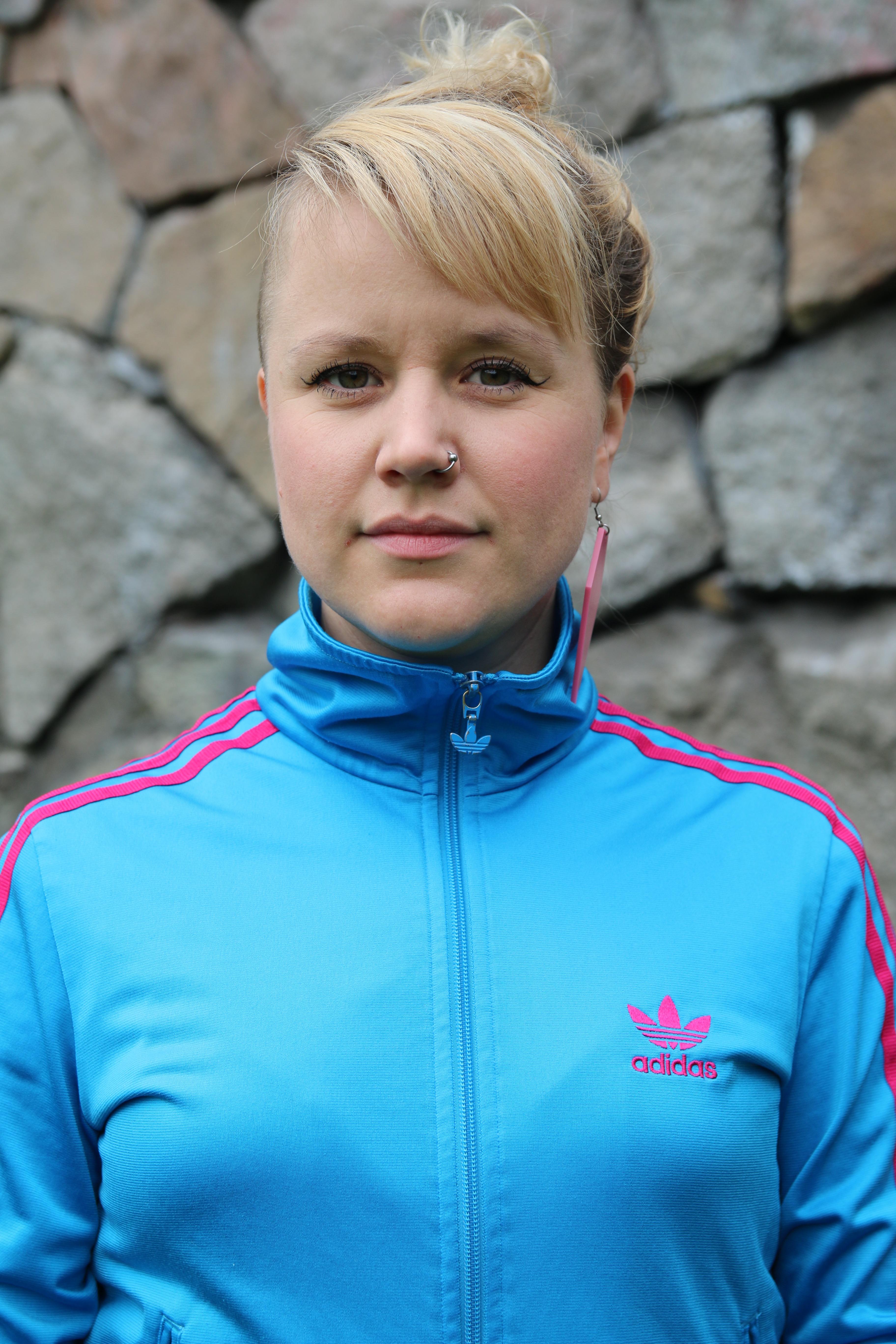 Anja, projektledare och kurator, har ljust uppsatt hår, blå tröja med rosa ränder och ett rosa örhänge. Hon tittar in i kameran. I bakgrunden är en stenmur.