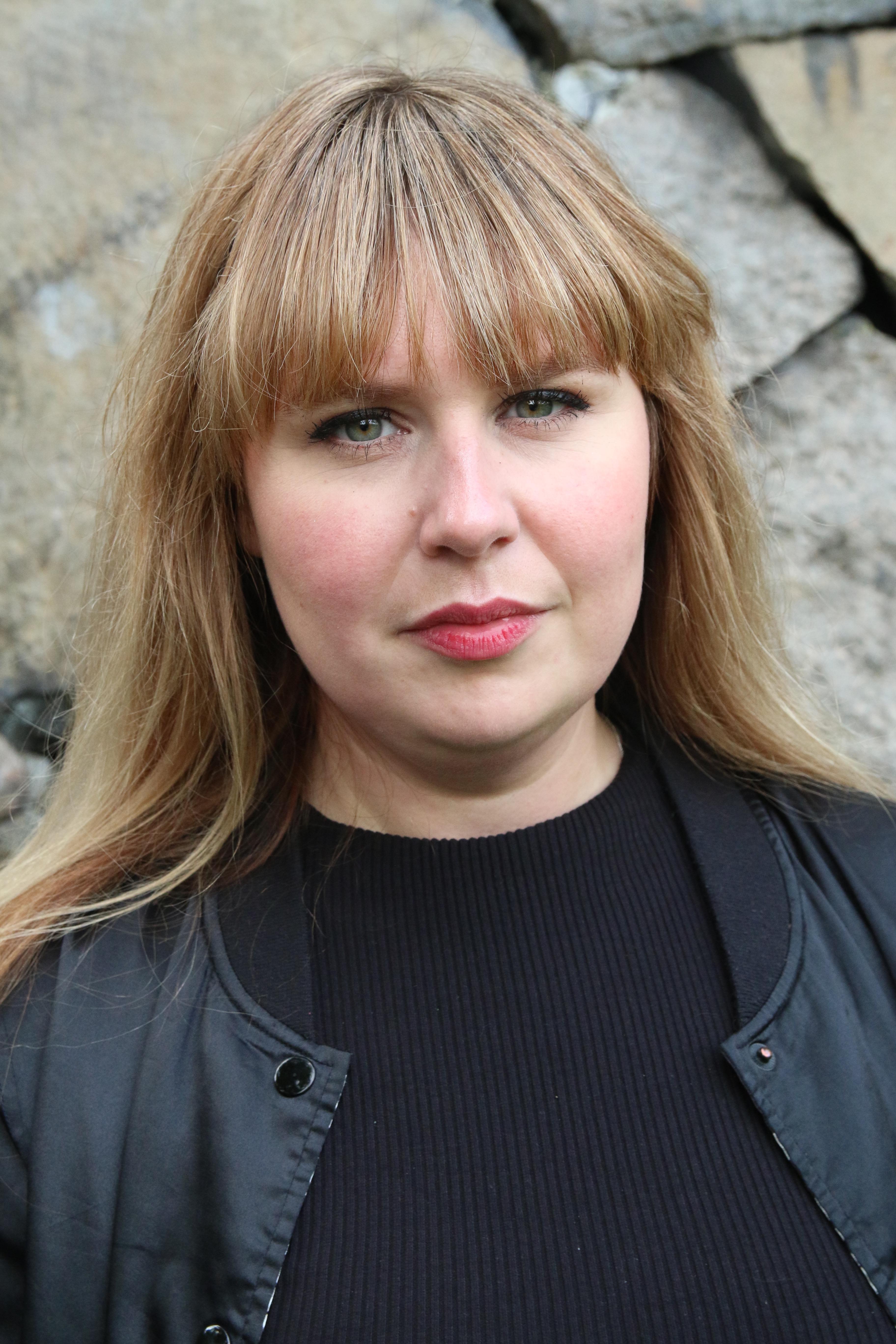 Malin, kommunikatör, har ljust långt hår med lugg, en svart tröja med en svart jacka över. Hon tittar in i kameran. I bakgrunden är en stenmur.
