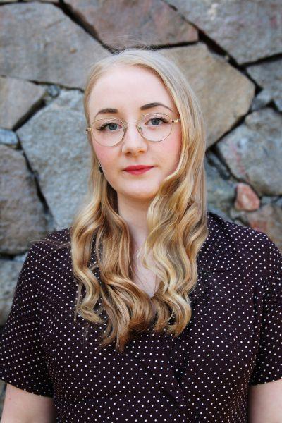 Virág, projektledare och kurator, har långt ljust hår och glasögon, samt en brun klänning med vita prickar. Hon tittar in i kameran. I bakgrunden är en stenmur.